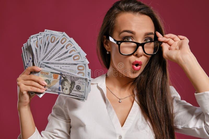 Brunette girl in glasses, wearing in a black short skirt and white blouse is posing holding a fan of hundred dollar. Lovely brunette girl with a long hair, in stock photography