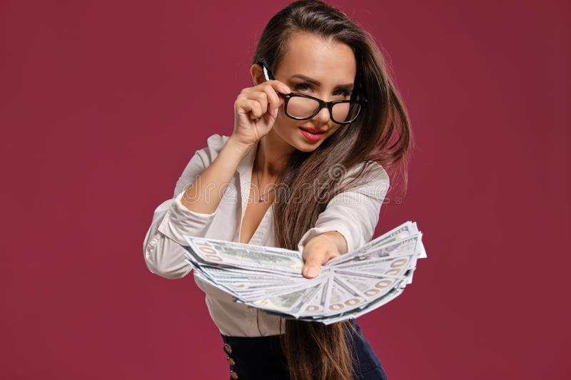 Brunette girl in glasses, wearing in a black short skirt and white blouse is posing holding a fan of hundred dollar. Lovely brunette woman with a long hair, in royalty free stock photos