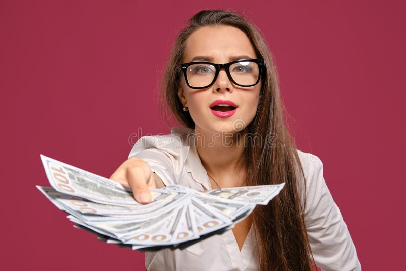 Brunette girl in glasses, wearing in a black short skirt and white blouse is posing holding a fan of hundred dollar. Pretty brunette female with a long hair, in royalty free stock images