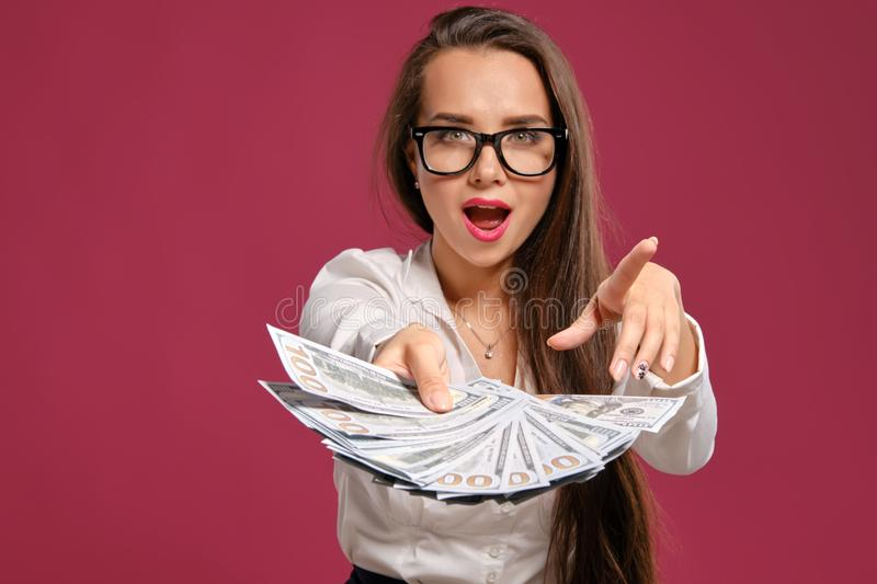 Brunette girl in glasses, wearing in a black short skirt and white blouse is posing holding a fan of hundred dollar. Pretty brunette girl with a long hair, in royalty free stock image