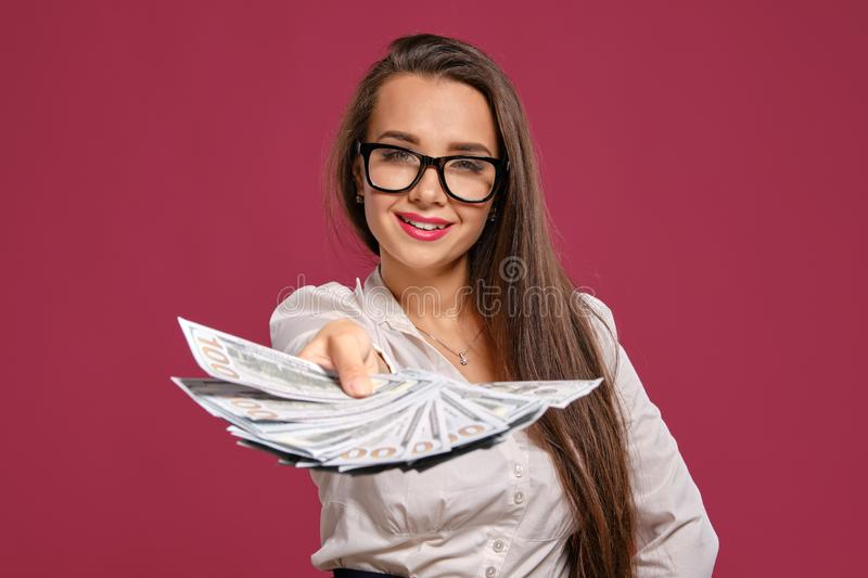 Brunette girl in glasses, wearing in a black short skirt and white blouse is posing holding a fan of hundred dollar. Pretty brunette woman with a long hair, in stock image