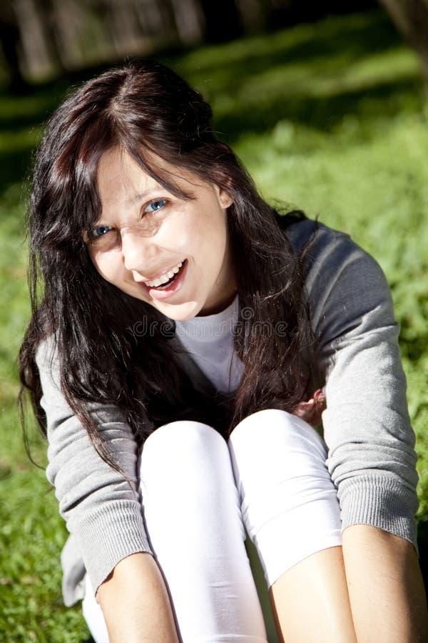 Brunette girl on green grass in the park. royalty free stock image