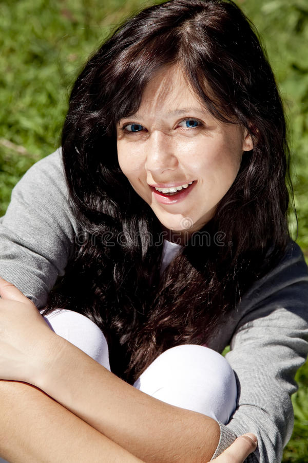 Brunette girl on green grass in the park. royalty free stock photo