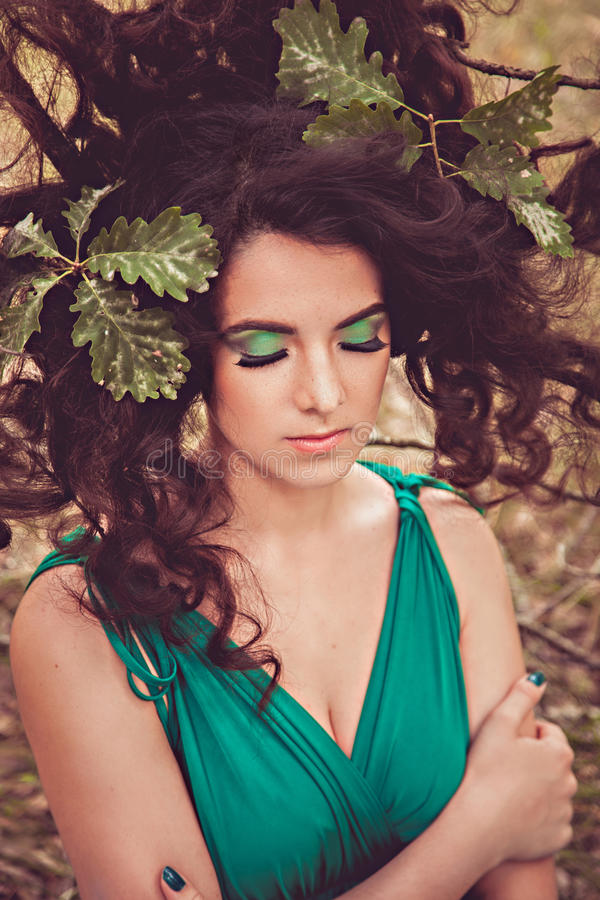 Brunette girl with hair on the branches stock image