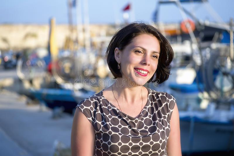 Brunette girl is happy on the waterfront of the Mediterranean sea royalty free stock photo