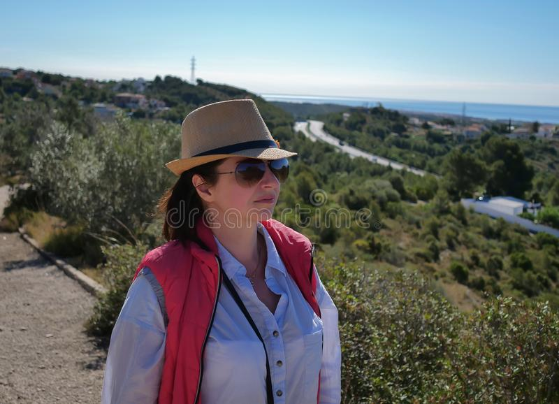 Brunette girl in a hat and sunglasses looks at the road away royalty free stock photography