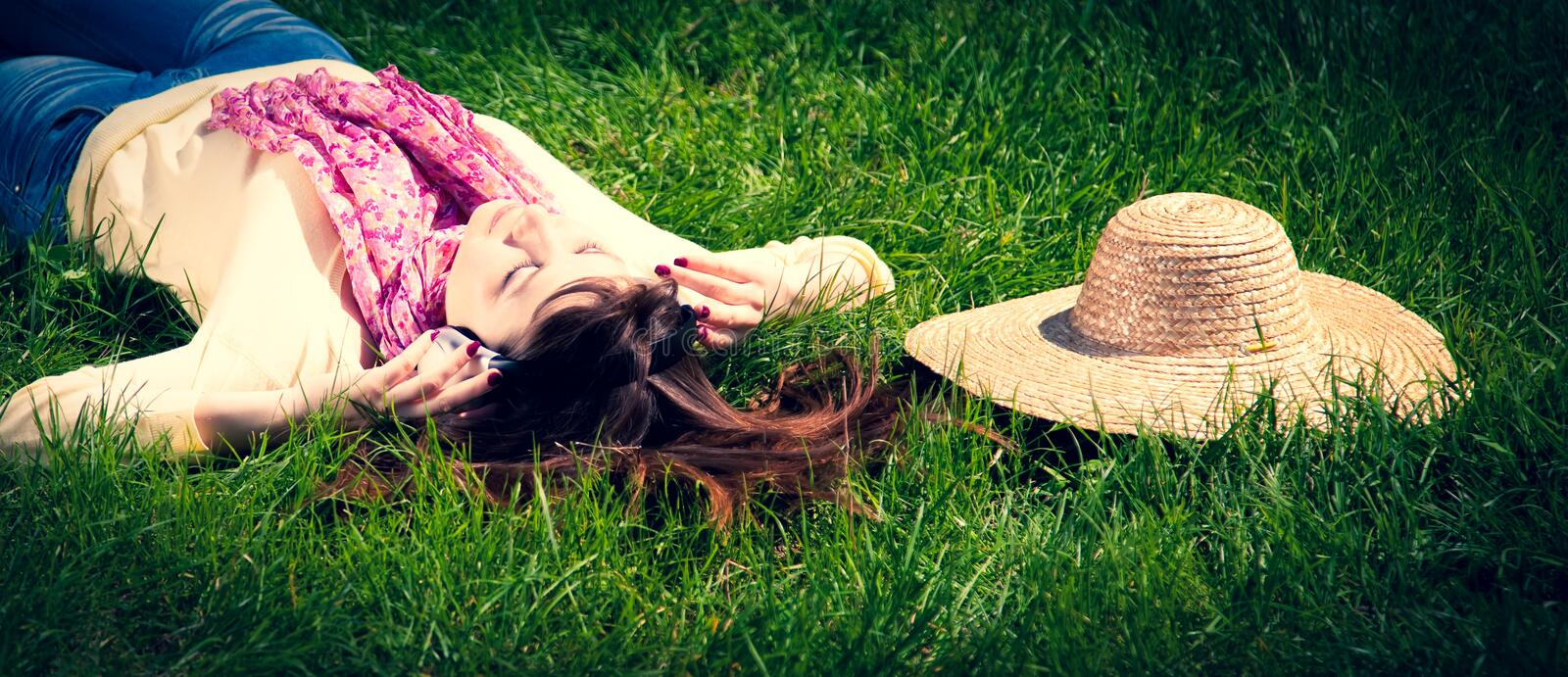 Brunette girl with headphones lies in park. royalty free stock photography