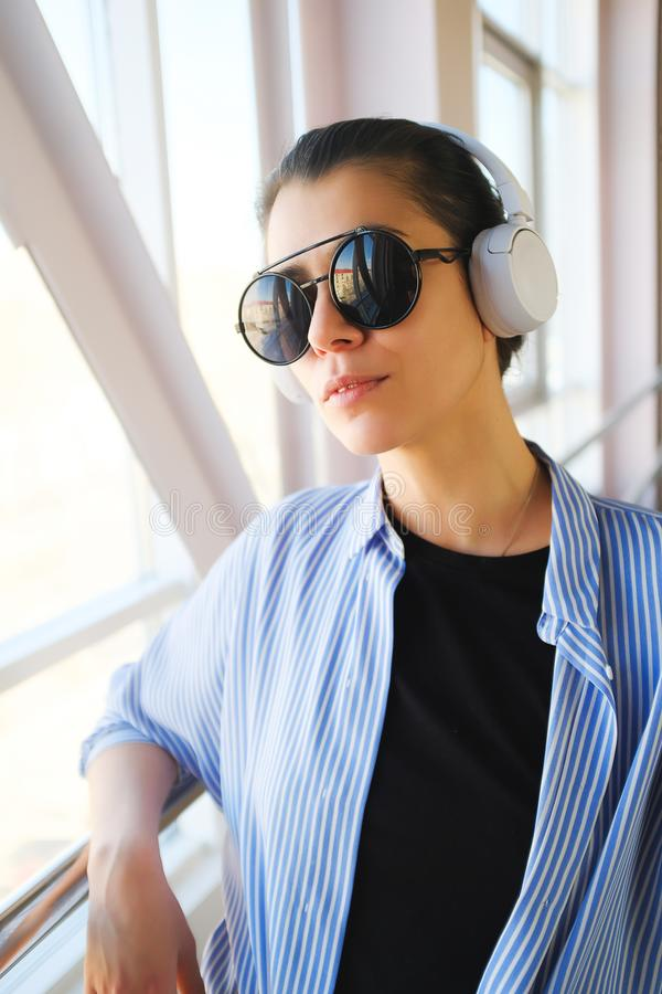 Brunette girl with headphones listening to music, while in the room, airport, office. Stylish fashionable young woman in glasses stock photo