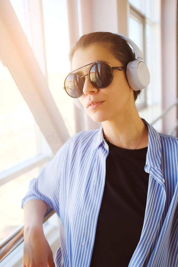 Brunette girl with headphones listening to music, while in the room, airport, office. Stylish fashionable young woman in glasses stock images