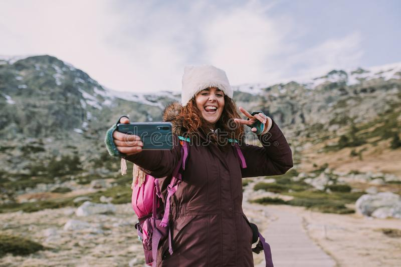 Brunette girl with her backpack and a hat on her head she takes a picture next to the mountains with a big smile on her mouth royalty free stock photo