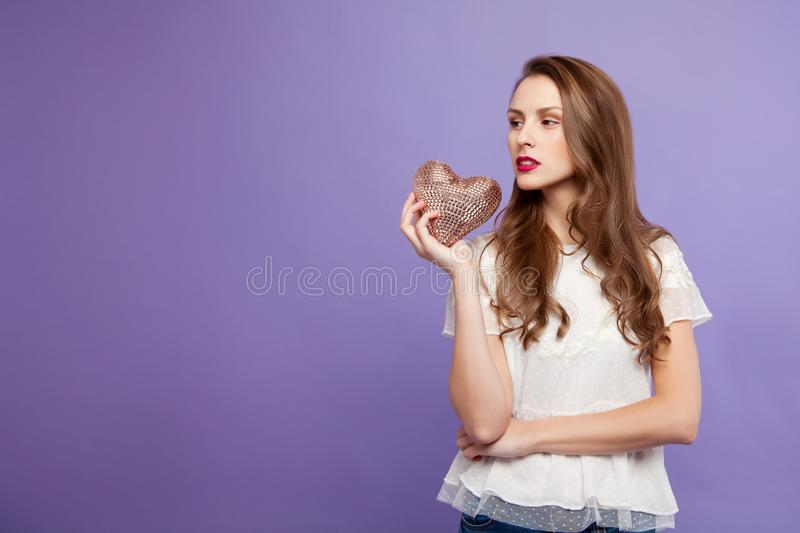 The brunette girl is holding a decorative heart in her hand. On a lilac background. concept for Valentine`s Day. place for text stock photo