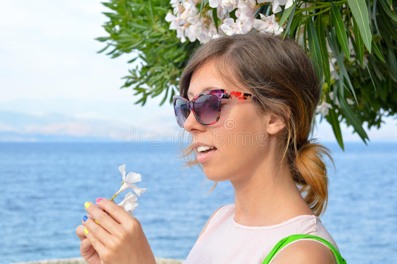Brunette girl holding a white flower with seaside in background. Young girl with sunglasses holding a white flower in her hand at the seaside royalty free stock images
