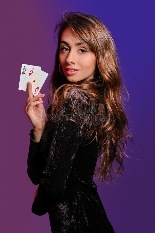 Free Brunette Girl In Black Velvet Dress Showing Two Playing Cards, Posing Sideways On Coloful Background. Gambling Royalty Free Stock Photos - 172145078