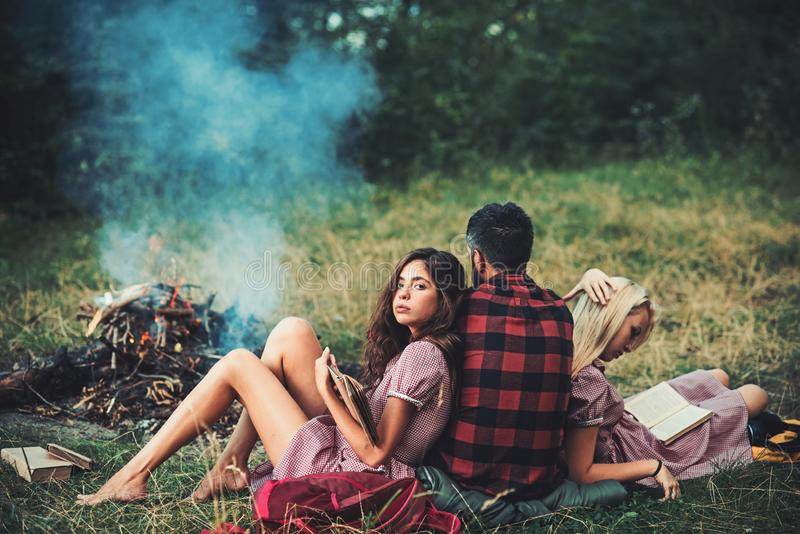 Brunette girl leaning on her boyfriend while reading book. Turn back guy looking at campfire. Young couple in love royalty free stock photo