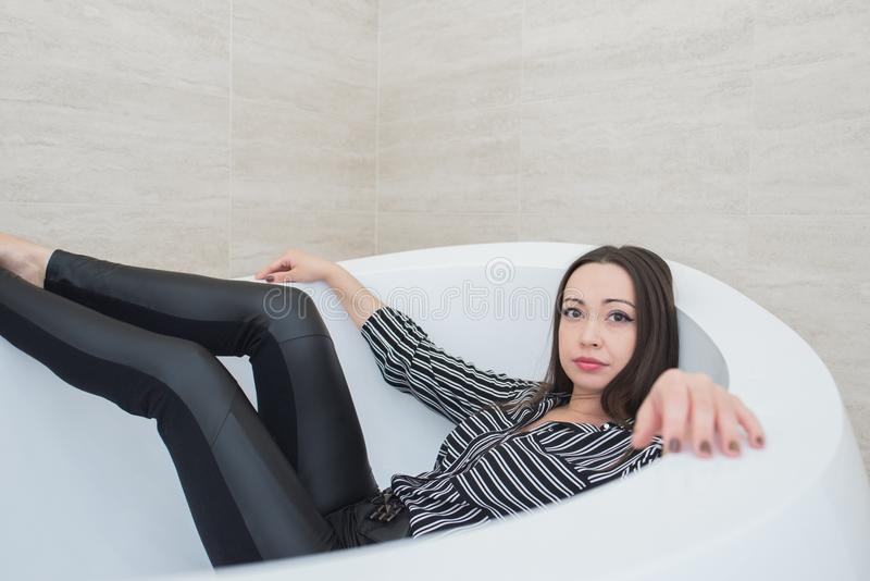 The brunette girl lies in a bathtub with a calm and peaceful expression. royalty free stock photo