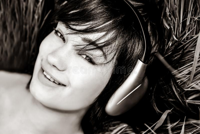 Brunette girl listening music at grass. royalty free stock images
