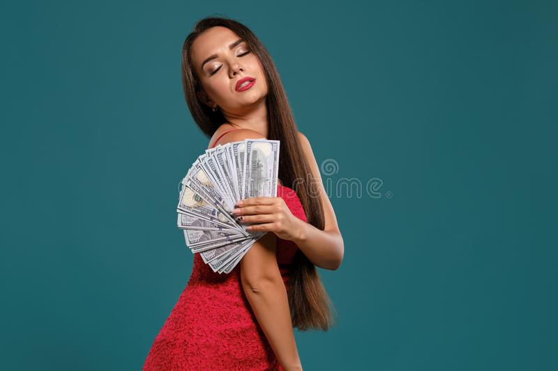 Brunette girl with a long hair, wearing a sexy red dress is posing holding a fan of hundred dollar bills against a blue. Attractive brunette female with a long stock images