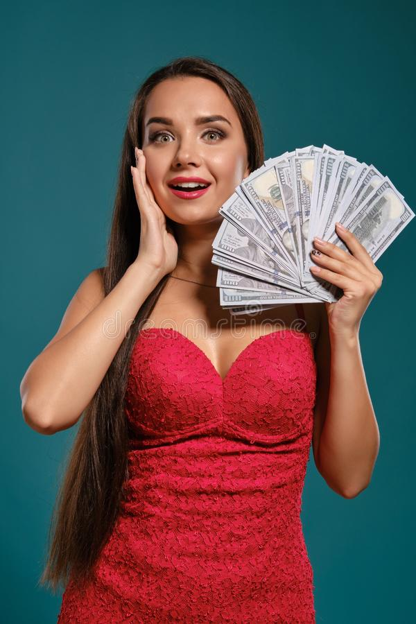 Brunette girl with a long hair, wearing a sexy red dress is posing holding a fan of hundred dollar bills against a blue. Attractive brunette lady with a long royalty free stock photography