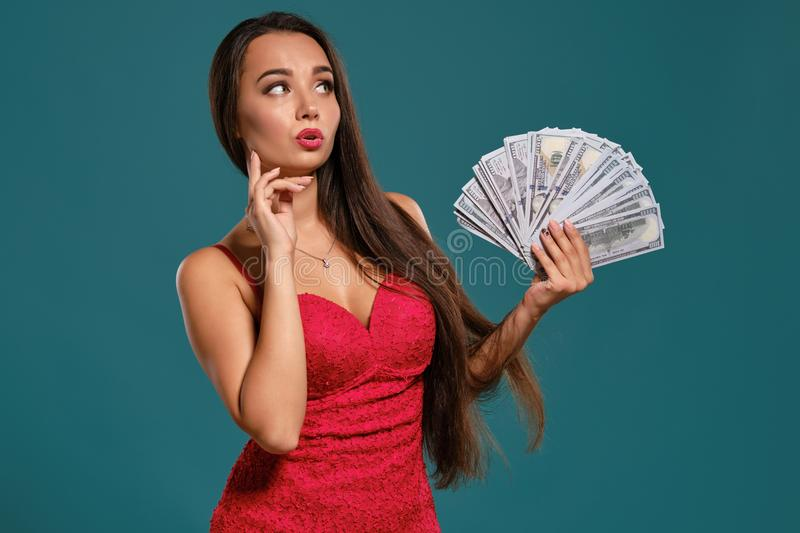 Brunette girl with a long hair, wearing a sexy red dress is posing holding a fan of hundred dollar bills against a blue. Attractive brunette woman with a long stock photo