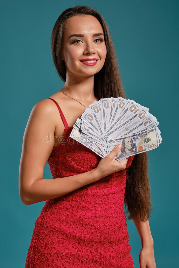 Brunette girl with a long hair, wearing a sexy red dress is posing holding a fan of hundred dollar bills against a blue. Beautiful brunette maiden with a long royalty free stock image