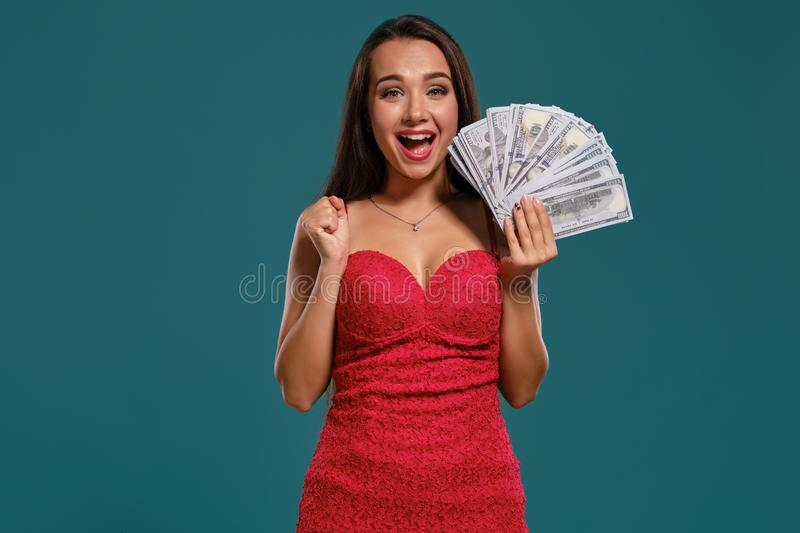Brunette girl with a long hair, wearing a sexy red dress is posing holding a fan of hundred dollar bills against a blue. Charming brunette lady with a long hair stock images