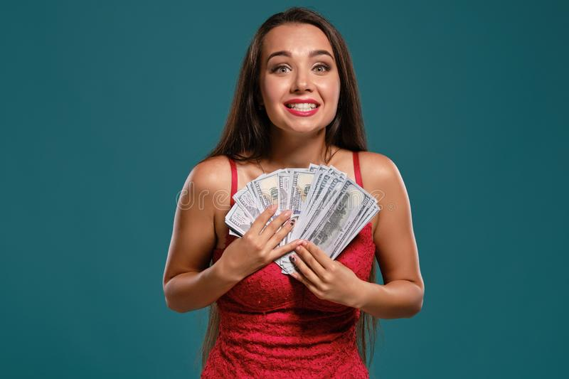 Brunette girl with a long hair, wearing a sexy red dress is posing holding a fan of hundred dollar bills against a blue. Charming brunette maiden with a long stock photo