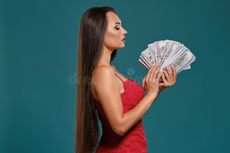 Brunette girl with a long hair, wearing a sexy red dress is posing holding a fan of hundred dollar bills against a blue. Charming brunette woman with a long hair royalty free stock photos