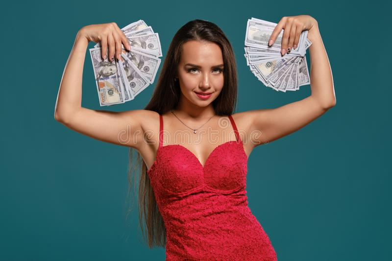 Brunette girl with a long hair, wearing a sexy red dress is posing holding a fan of hundred dollar bills against a blue. Cute brunette lady with a long hair royalty free stock image