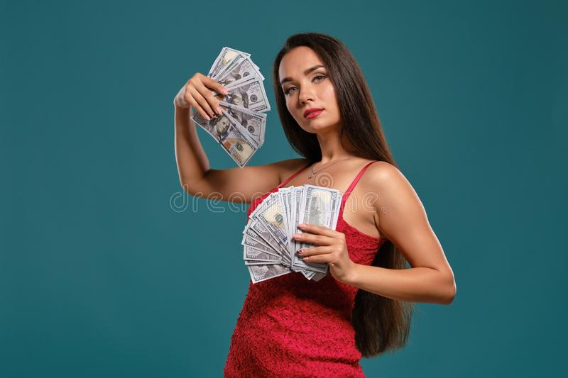 Brunette girl with a long hair, wearing a sexy red dress is posing holding a fan of hundred dollar bills against a blue. Cute brunette girl with a long hair stock photography