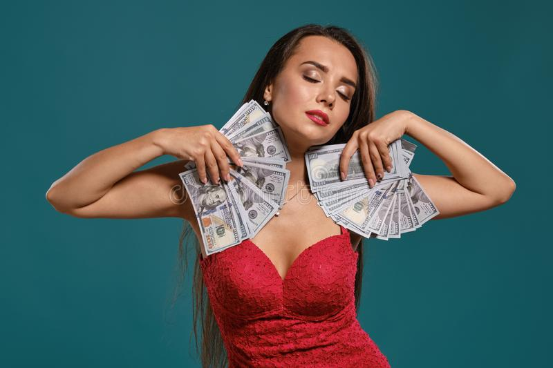 Brunette girl with a long hair, wearing a sexy red dress is posing holding a fan of hundred dollar bills against a blue. Cute brunette maiden with a long hair stock photo
