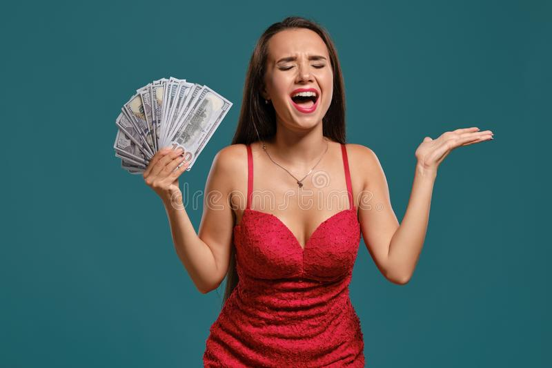 Brunette girl with a long hair, wearing a sexy red dress is posing holding a fan of hundred dollar bills against a blue. Elegant brunette girl with a long hair stock photography