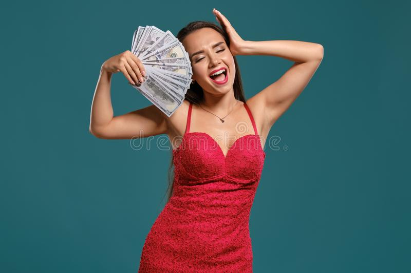 Brunette girl with a long hair, wearing a sexy red dress is posing holding a fan of hundred dollar bills against a blue. Elegant brunette female with a long hair stock photo