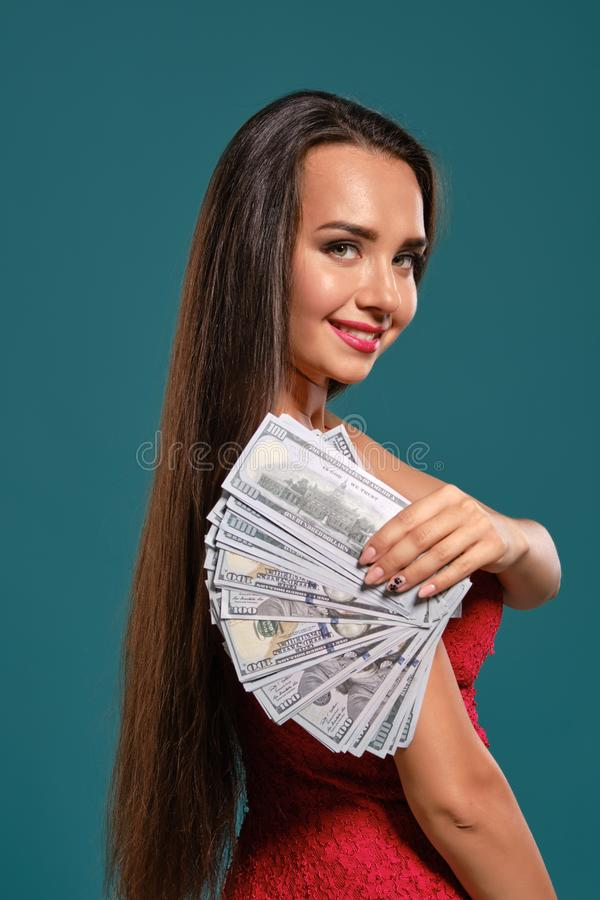 Brunette girl with a long hair, wearing a sexy red dress is posing holding a fan of hundred dollar bills against a blue. Elegant brunette maiden with a long hair royalty free stock photo