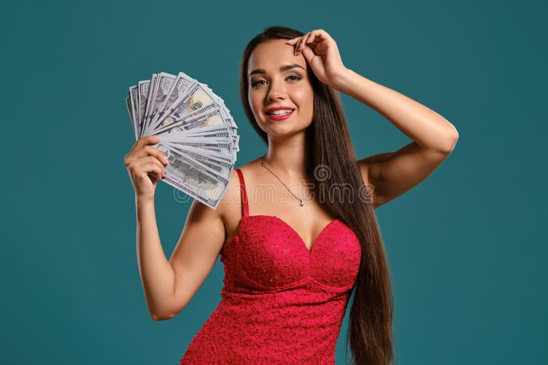 Brunette girl with a long hair, wearing a sexy red dress is posing holding a fan of hundred dollar bills against a blue. Gorgeous brunette female with a long royalty free stock photo