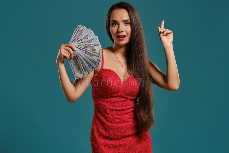 Brunette girl with a long hair, wearing a sexy red dress is posing holding a fan of hundred dollar bills against a blue. Gorgeous brunette lady with a long hair stock photography