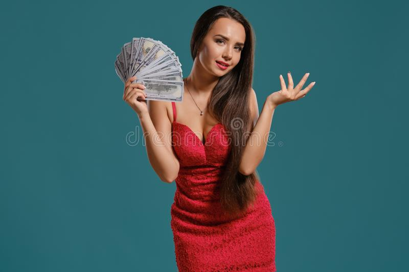 Brunette girl with a long hair, wearing a sexy red dress is posing holding a fan of hundred dollar bills against a blue. Gorgeous brunette girl with a long hair stock photos