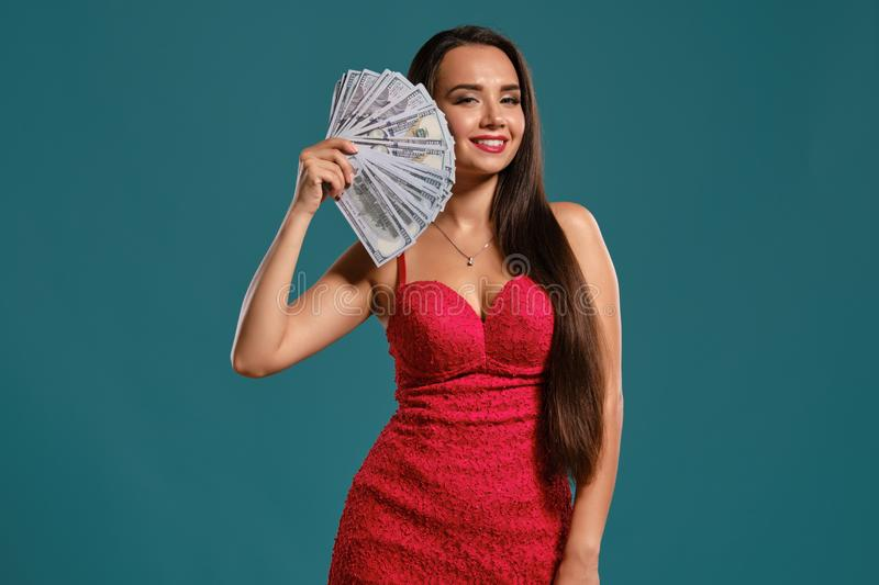 Brunette girl with a long hair, wearing a sexy red dress is posing holding a fan of hundred dollar bills against a blue. Gorgeous brunette woman with a long hair royalty free stock images