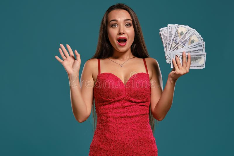 Brunette girl with a long hair, wearing a sexy red dress is posing holding a fan of hundred dollar bills against a blue. Pretty brunette girl with a long hair stock photography