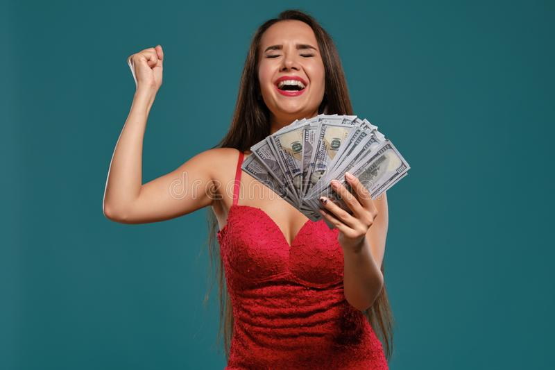 Brunette girl with a long hair, wearing a sexy red dress is posing holding a fan of hundred dollar bills against a blue. Pretty brunette female with a long hair stock images