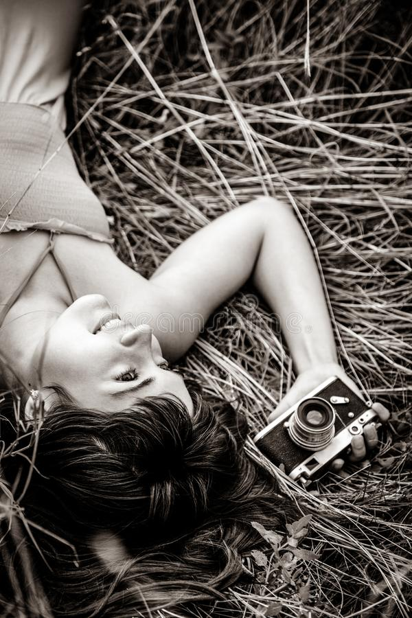 Brunette girl lying at grass with camera in summer time royalty free stock photography