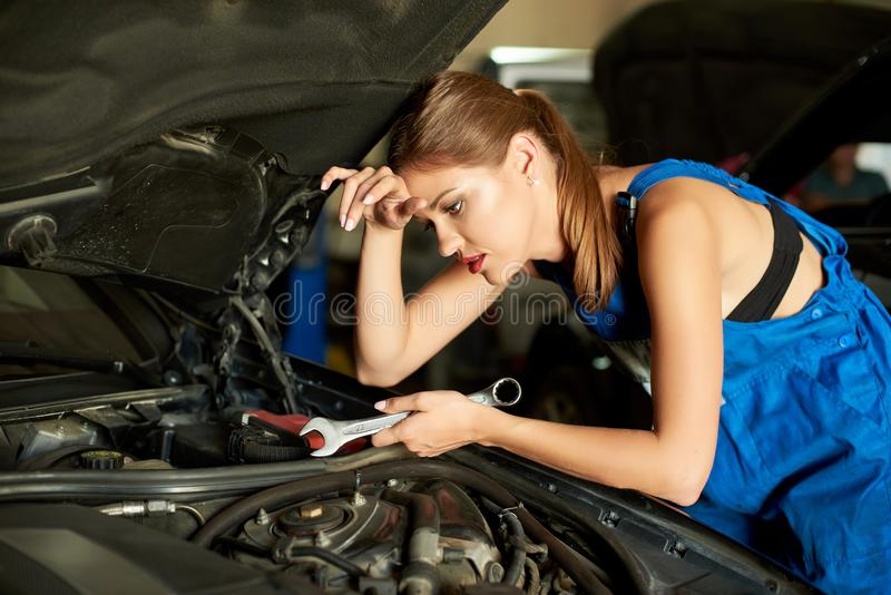 Brunette girl mechanics repairing or inspecting a car. And holds a spanner in her hand. Girl is dressed in working clothes royalty free stock photos