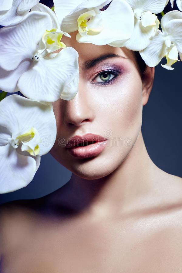 Brunette girl with Orchid flowers on the face and chest, beauty portrait of a perfect makeup, beautiful eyes and plump lips royalty free stock photos
