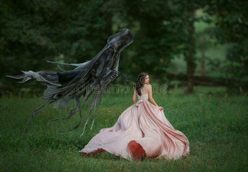 Brunette girl in a panic runs away from death. Dark evil curse haunting woman. Enchanted princess in a luxurious, flying stock photos