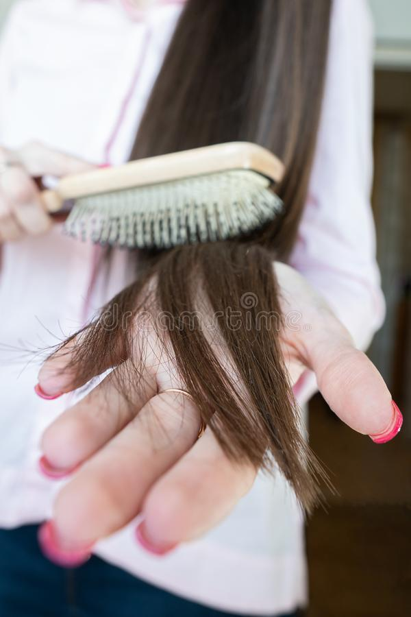 Brunette girl in a pink shirt is combing her beautiful long hair comb stock photos