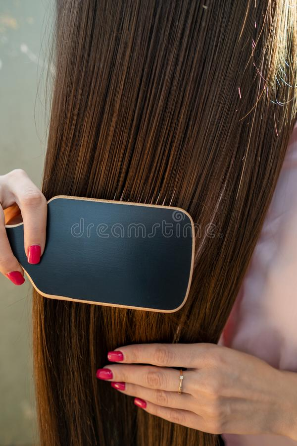 Brunette girl in a pink shirt is combing her beautiful long hair comb royalty free stock image