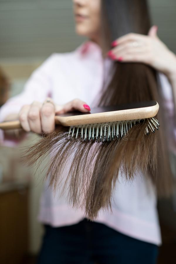 Brunette girl in a pink shirt is combing her beautiful long hair comb royalty free stock photography