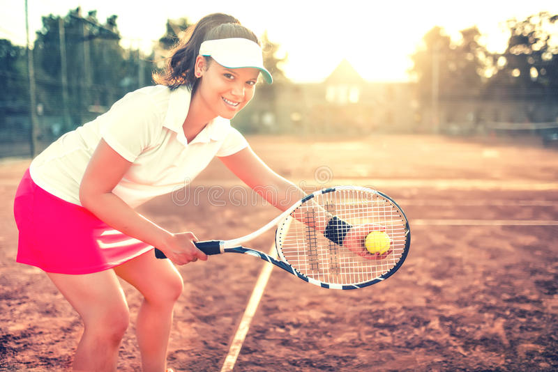Brunette girl playing tennis with racket, balls and sports equipment. Close up portrait of beautiful woman on tennis cou royalty free stock photography