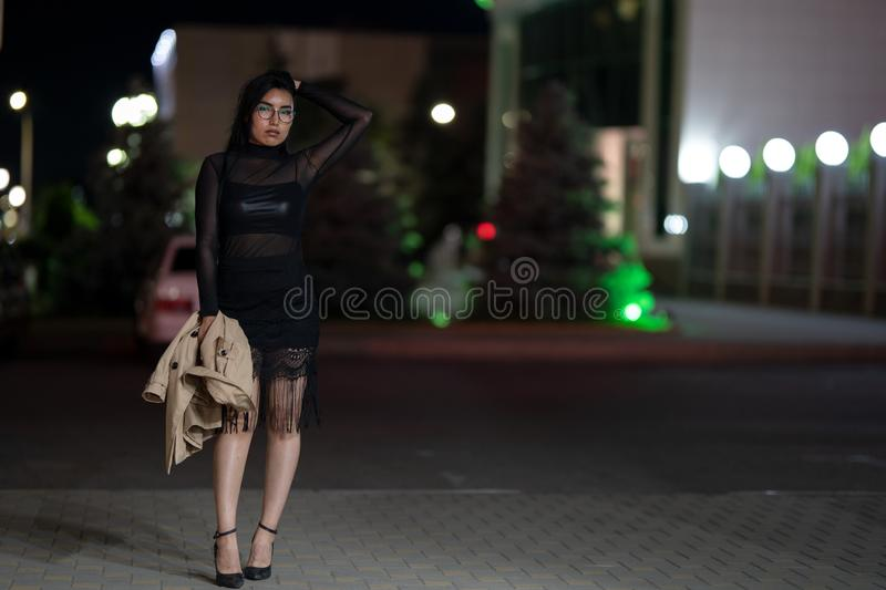 Brunette girl poses against the evening night city, colorful lights illuminate the shopping windows. A beautiful oriental girl from Turkmenistan in the evening royalty free stock photography