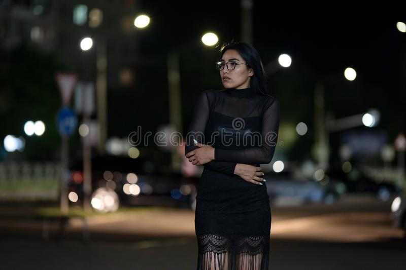 Brunette girl poses against the evening night city, colorful lights illuminate the shopping windows. A beautiful oriental girl from Turkmenistan in the evening royalty free stock photos