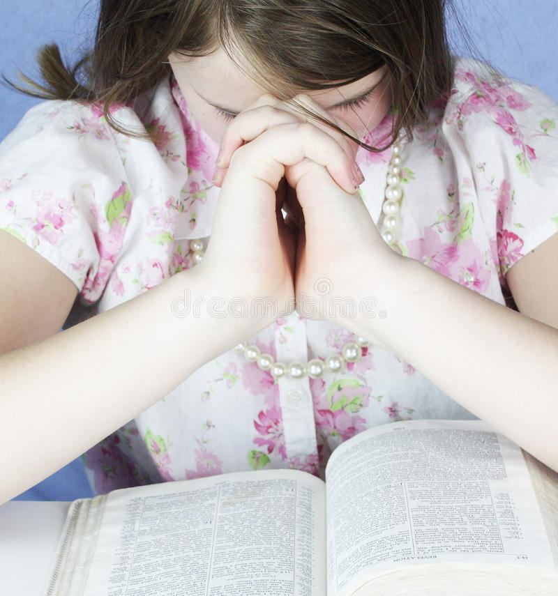Brunette Girl Prays With Bible. Young girl reads her bible and prays stock image